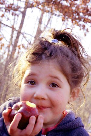 Young girl eating apple outside Stock Photo