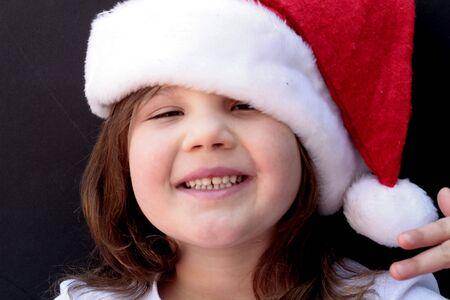 face close up: Girl in Santa hat waiting for Santa