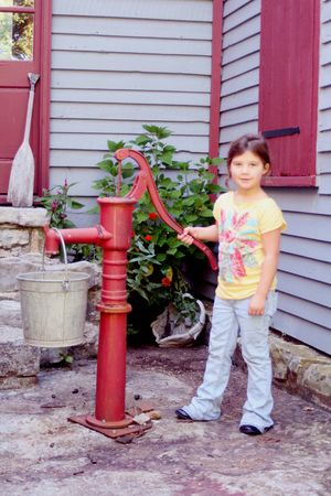 Little girl pumping water from old water pump photo