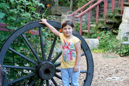 Little girl standing by a big wagon wheel photo