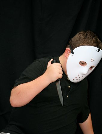 Young boy in horror halloween mask and knife photo