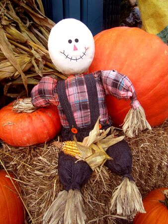Fall decorations of pumpkins, scarecrow sitting on bale of hay photo