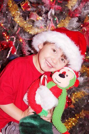 Cute baby boy in Santa hat under Christmas tree