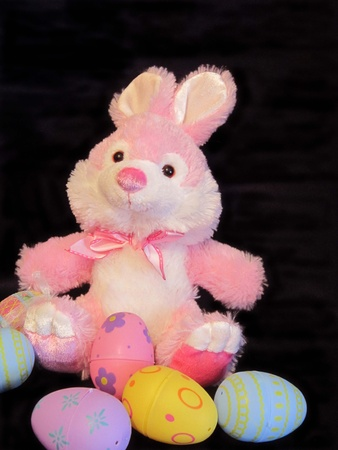 Pink Easter bunny with colored eggs Stock Photo