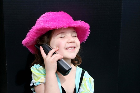 Pretty little girl in pink hat using the telephone photo