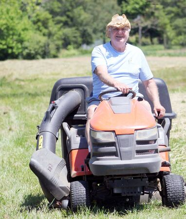 mowing grass: Senior man mowing grass on riding lawnmower