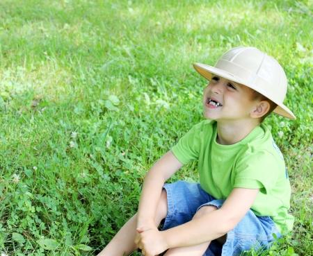 Little boy sitting on grass