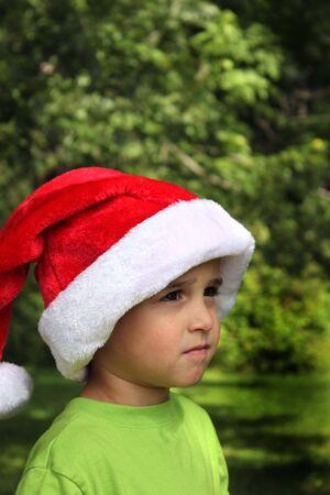 Pretty baby boy in green shirt and Santa hat