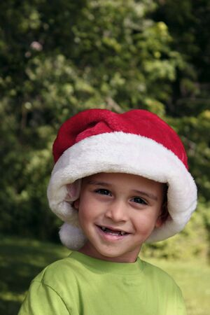 Young boy wearing Santa hat and smiling Stock Photo