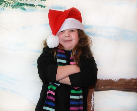 Cute little girl in the snow with Santa hat photo