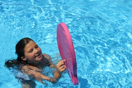 Cute little girl playing in the pool