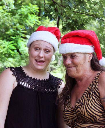 Two women wearing Santa Hats