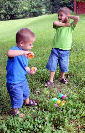 Two brothers finding Easter Eggs outside