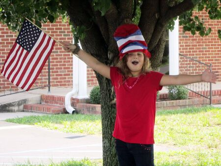 Pretty little girl wearing 4th of July hat with flag Stock Photo