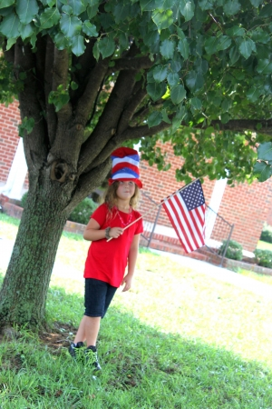 Little girl holding 4th of July flag photo