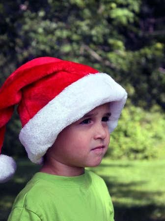 Baby boy in Santa hat outside