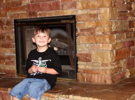 Cute little boy sitting on fireplace