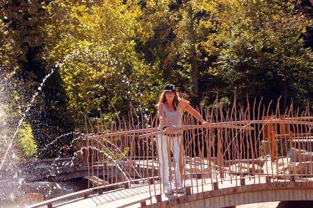 Senior woman on bridge with water spouts