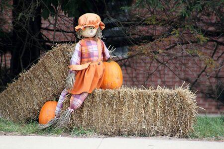 Halloween scarecrow sitting on bale of hay Stock Photo