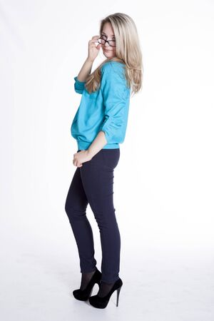 Beautiful blonde in a blue blouse and trousers Beautiful blonde in a blue blouse and trousers rehearsing photoshoot Stock Photo