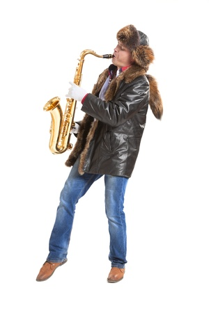 Young man in outerwear playing on saxophone photo