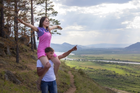 young man holding the girl on a neck and looking at nature photo