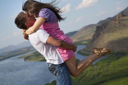 幸せな若いカップルが山でキス