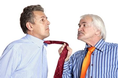 白い背景の上の若い男にネクタイを引っ張って実業家