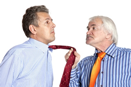 businessman pulling a tie to younger man on white background Standard-Bild