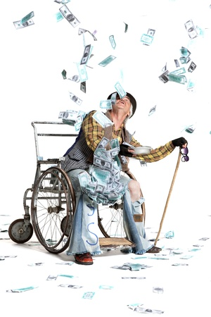 homeless man with a wheelchair with a lot of money on a white background Stock Photo