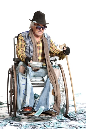 shoked:  homeless man with a wheelchair with a lot of money on a white background Stock Photo