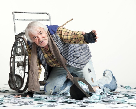 homeless man with a wheelchair with a lot of money on a white background 写真素材
