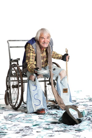 homeless man with a wheelchair with a lot of money on a white background Standard-Bild