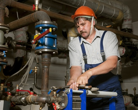 Plumber with pipe wrench works photo