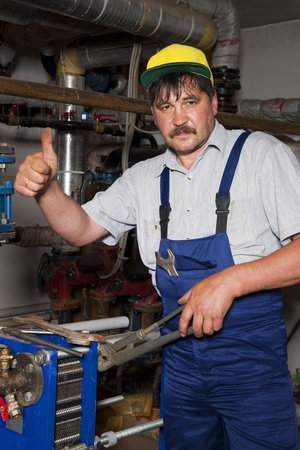 Plumber working with tubes and giving thumb up photo