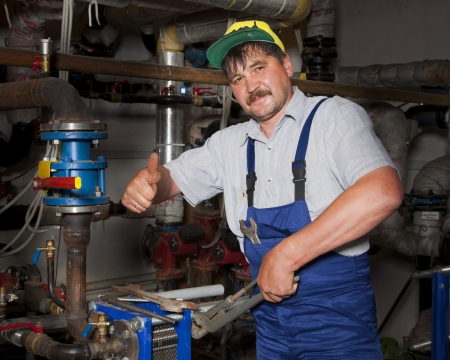 Plumber working with tubes and giving thumb up Stock Photo