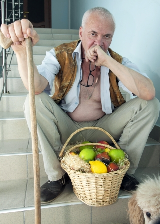 Sad man sitting on the stairs with a dog and a basket of fruit photo
