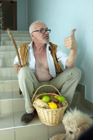 an sitting on the stairs with a dog and a basket of fruit and shows thumb up photo