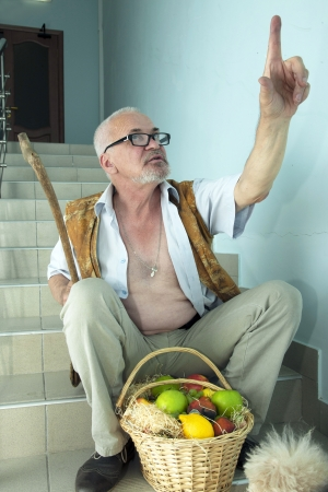 Emotional man sitting on the stairs and shows up with a dog and a basket of fruit photo