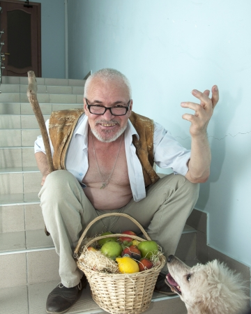 Emotional man sitting on the stairs with a dog and a basket of fruit photo