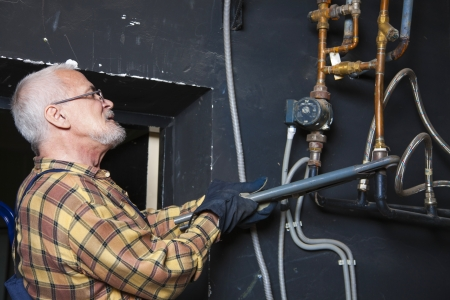Gray-haired plumber repairing pipes photo