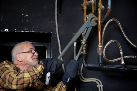 Gray-haired plumber repairing pipes