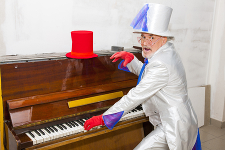 Magician in a suit playing the piano photo