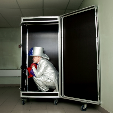 Magician in a white suit with hat sitting in a box before the show photo