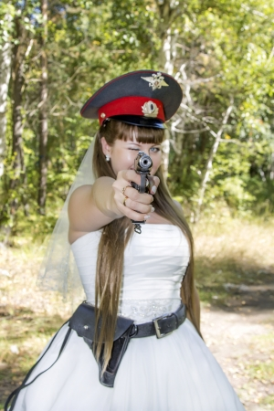 beautiful young bride in a police cap and a gun photo