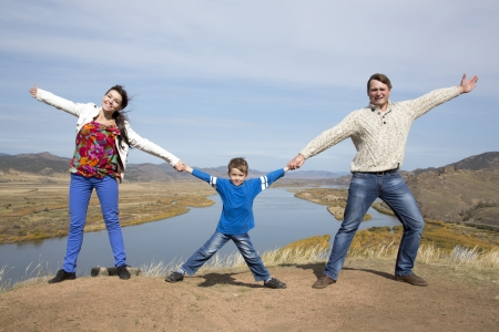 happy father and mother with son holding hands together on the mountain with lake in the background photo
