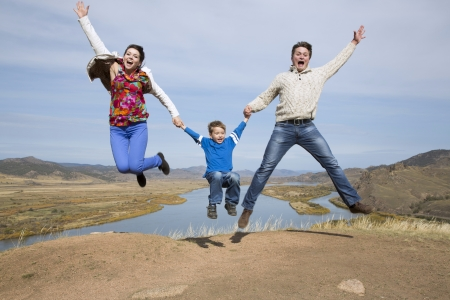 happy father and mother with son jumping on the mountain with lake in the background photo