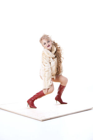 curly-haired woman in a fur coat and red boots posing on the parquet on white background photo
