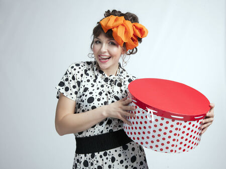 polka dot dress: Young happy girl in a polka dot dress and bow on her head holding red gift box on a gray background