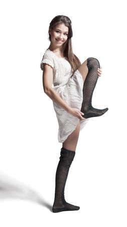 girl in white dress training her leg on white background photo